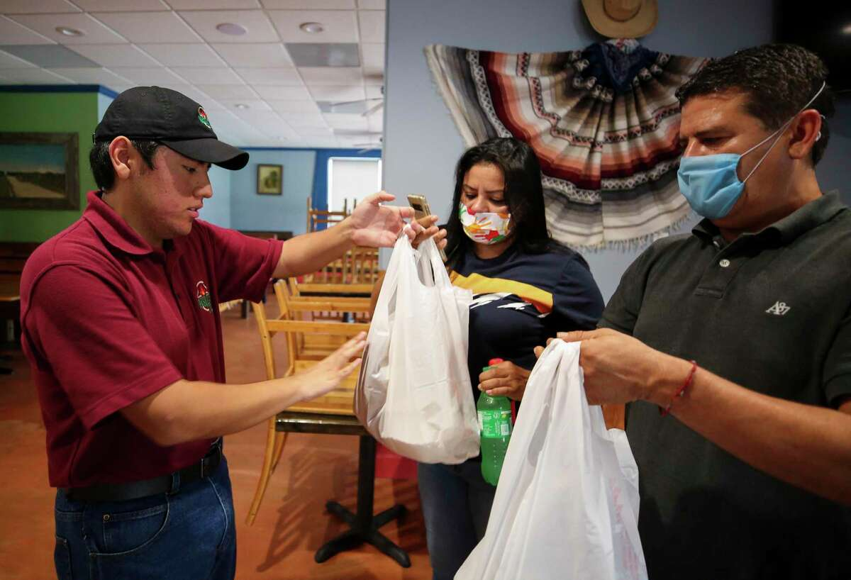 Alex Miranda, left, hands off a to-go food order to customers inside The Mesquite Grill on Monday, April 6, 2020, in Houston. Harris County last week launched a $10 million small business loan fund to help owners hurt by the coronavirus pandemic.