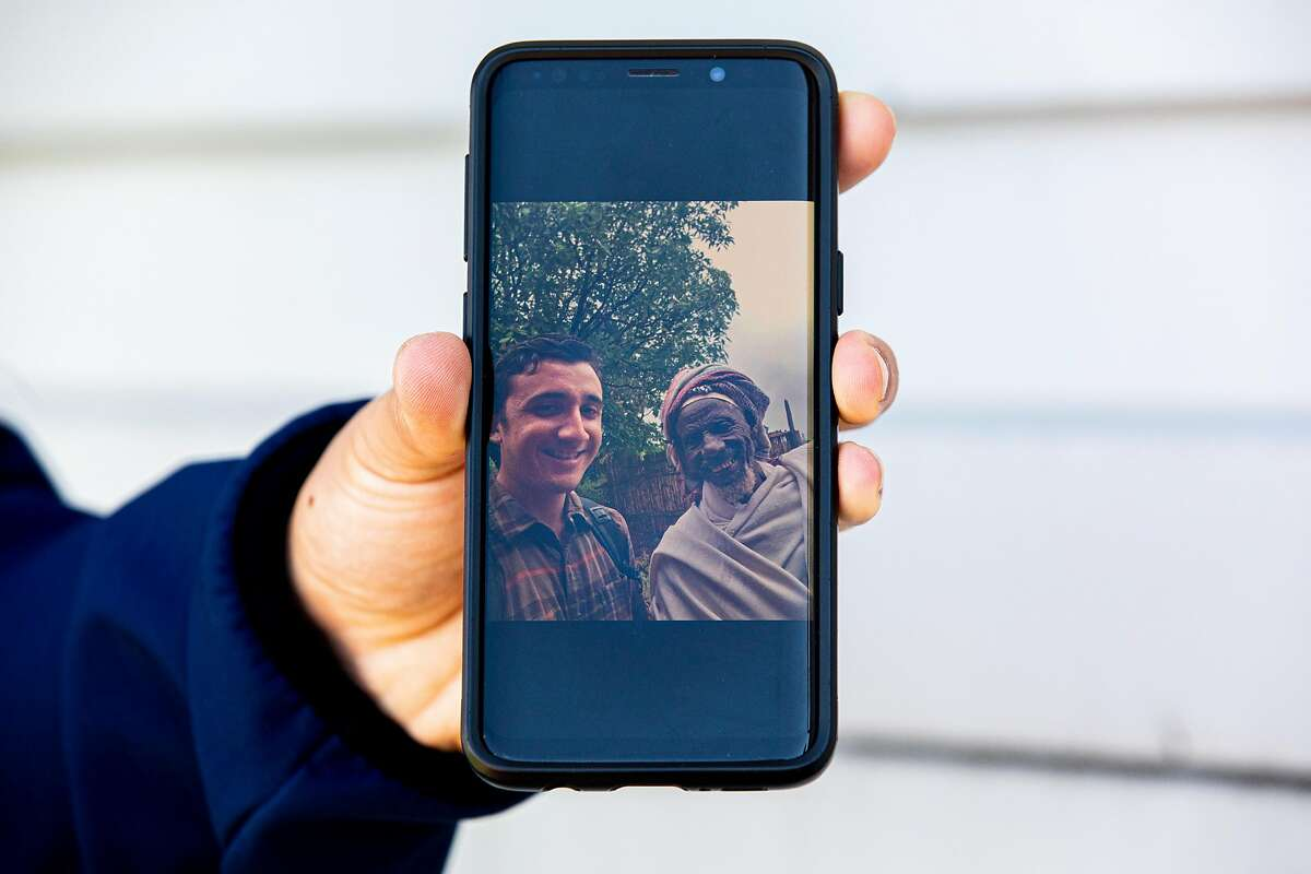 Eddy Holman shares a photo of him and town elder Father Maachaa displayed on his phone while in San Lorenzo, Calif. Tuesday, April 7, 2020. Eddy was a PeaceCorps volunteer in Ethiopia who was evacuated from the country because of COVID-19. He's staying at the home of his mother's boyfriend and using her cell phone as resettles into life in the Bay Area and waits for the program to resume.
