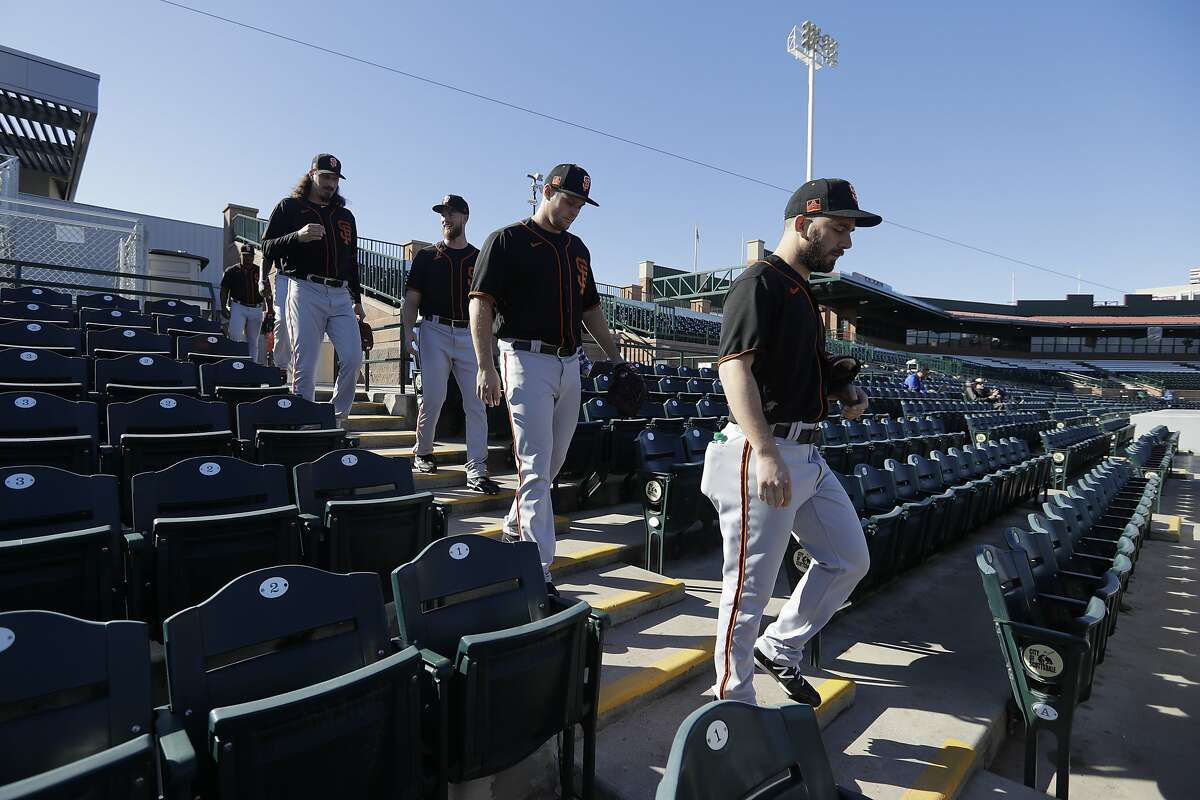 San Francisco Giants' Sam Moll, front, leads a group of players to the field during spring training baseball practice, Friday, Feb. 14, 2020, in Scottsdale, Ariz. (AP Photo/Darron Cummings)