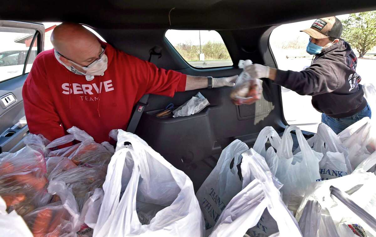 West Haven, Connecticut - Tuesday, April 07, 2020: Elder and outreach coordinator Paul Bronson, left, and Ken Bencivengo, right, both members of the Vertical Church in West Haven who volunteer in the Vertical Church emergency food pantry, fill up bags of food into a City of West Haven car driven by West Haven Public Works Commissioner Tom McCarthy that will eventually be delivered to vulnerable seniors and needy families in the greater New Haven area during the Covid-19 / Coronavirus pandemic in a joint collaboration with the City of West Haven, the City of New Haven, the West Haven Rotary Club and Westies Cares. Approximately 375 homebound seniors and approximately 1500 families are served.