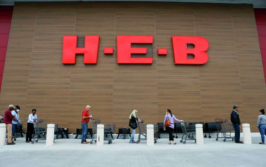 H-E-B employee Chermane Goldson sanitizes customers carts as they wait outside for the store to open, Wednesday, March 25, 2020, at the H-E-B in Bellaire. Photo: Mark Mulligan, Houston Chronicle / Staff Photographer / © 2020 Mark Mulligan / Houston Chronicle
