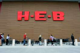 H-E-B employee Chermane Goldson sanitizes customers carts as they wait outside for the store to open, Wednesday, March 25, 2020, at the H-E-B in Bellaire.