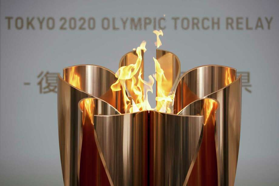 """In this March 24, 2020, file photo, the Olympic Flame burns during a ceremony in Fukushima City, Japan. The Olympic flame is going to be on display until the end of April in Japan's northeastern prefecture of Fukushima. Tokyo Olympic and prefecture officials held an official """"handover ceremony""""on Wednesday, April 1, at the J-Village National Training Center in Fukushima.(AP Photo/Jae C. Hong, File) / Copyright 2019 The Associated Press. All rights reserved"""
