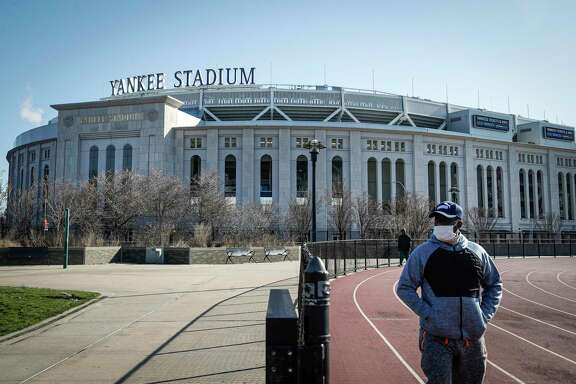 A pedestrian walks a running track while wearing a surgical mask near Yankee Stadium as it remains closed due to COVID-19 concerns, Thursday, March 26, 2020, in the Bronx borough of New York. To baseball fans, opening day is an annual rite of spring that evokes great anticipation and warm memories. This year's season was scheduled to begin Thursday, but there will be no games for a while because of the coronavirus outbreak. Major League Baseball has postponed opening day until mid-May at the earliest. (AP Photo/John Minchillo)