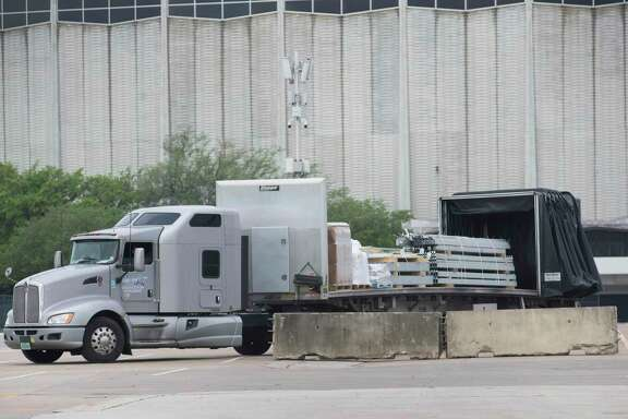 Workers set up a makeshift field hospital at NRG Park in preparation for an expected surge of COVID-19 patients in Harris County Tuesday, April 7, 2020, at Orange Lot in Houston.