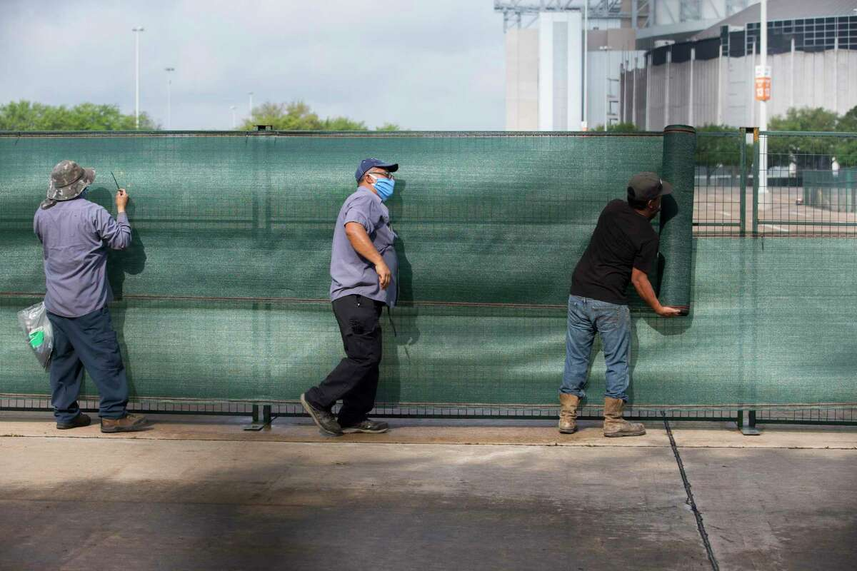 Workers cover fences while setting up a makeshift field hospital at NRG Park in preparation for an expected surge of COVID-19 patients in Harris County Tuesday, April 7, 2020, at Orange Lot in Houston.