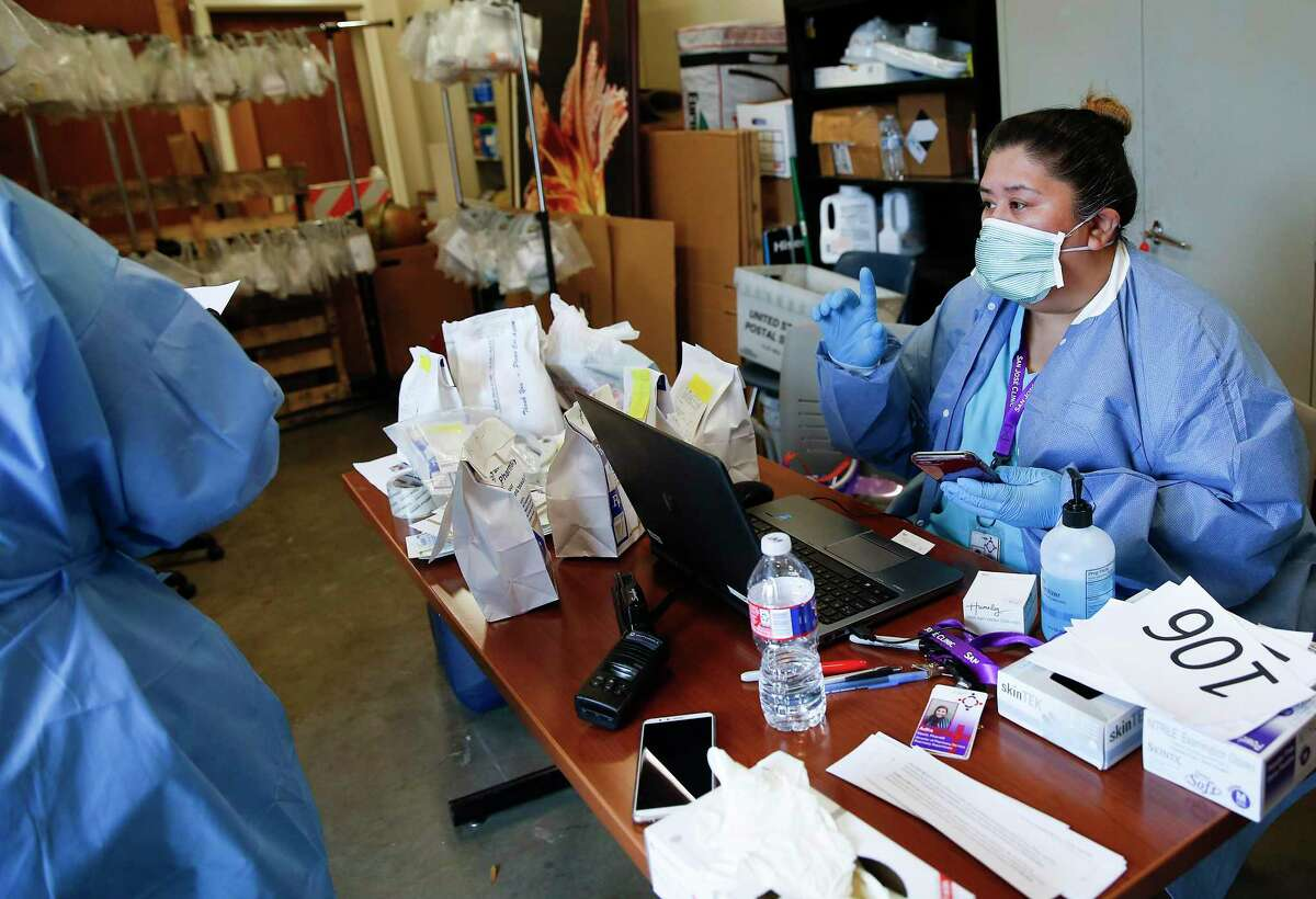 Pharmaceutical technician Norma Ollivares makes a call about a script at the San José Clinic in the Midtown neighborhood in Houston as they distribute 90-day prescriptions through a drive thru for their patients on Thursday, April 2, 2020.