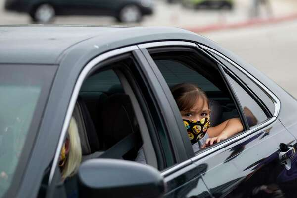 A young girl peers out the window of her vehicle while wearing an emoji pattern mask during the San Antonio Food Bank drive-through food distribution event April 7, 2020 in the Toyota Field parking lot in San Antonio. Mayor Ron Nirenberg and County Judge Nelson Wolff are urging San Antonio area residents to continue wearing masks and maintaining a 6-foot social distance from others when out in public to prevent a resurgence of the deadly novel coronavirus.