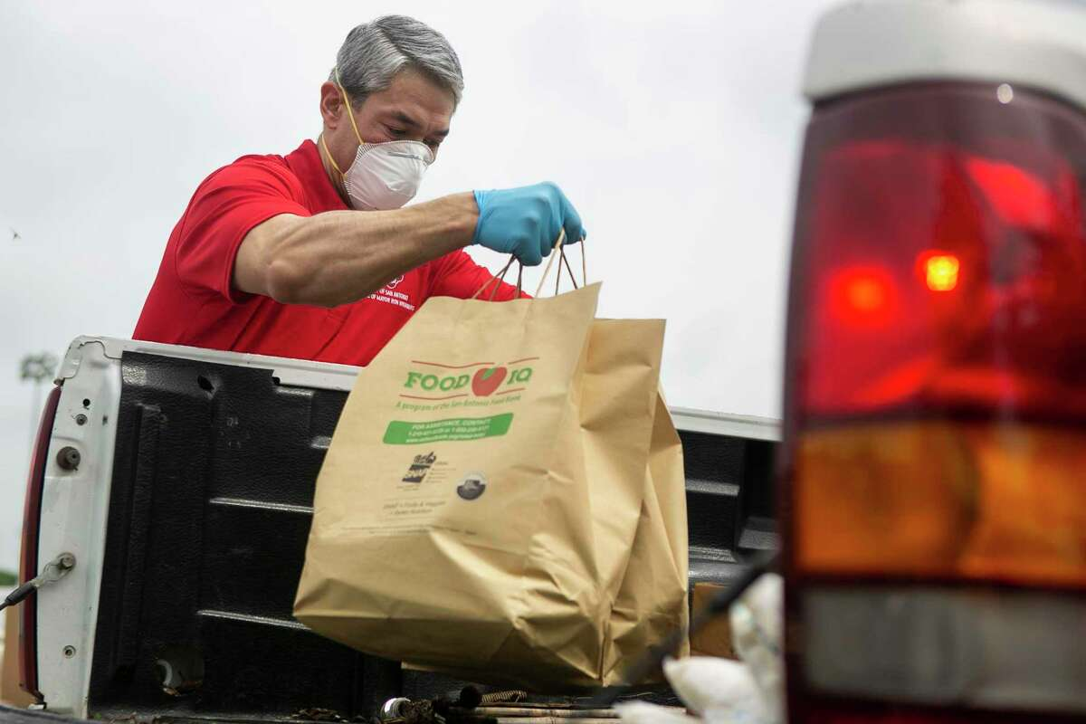 San Antonio Mayor Ron Nirenberg reaches for a bag of produce to give out with food during the San Antonio Food Bank drive-through food distribution on Tuesday, April 7, 2020, in the Toyota Field parking lot in San Antonio, Texas.
