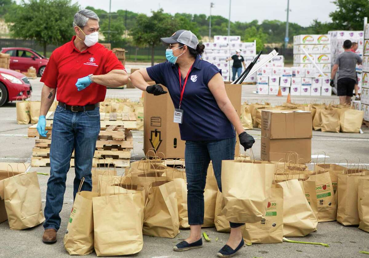 Mayor Ron Nirenberg elbow bumps with a volunteer during a San Antonio Food Bank distribution last month. He has risen to the moment, but also looked beyond it for the city. .