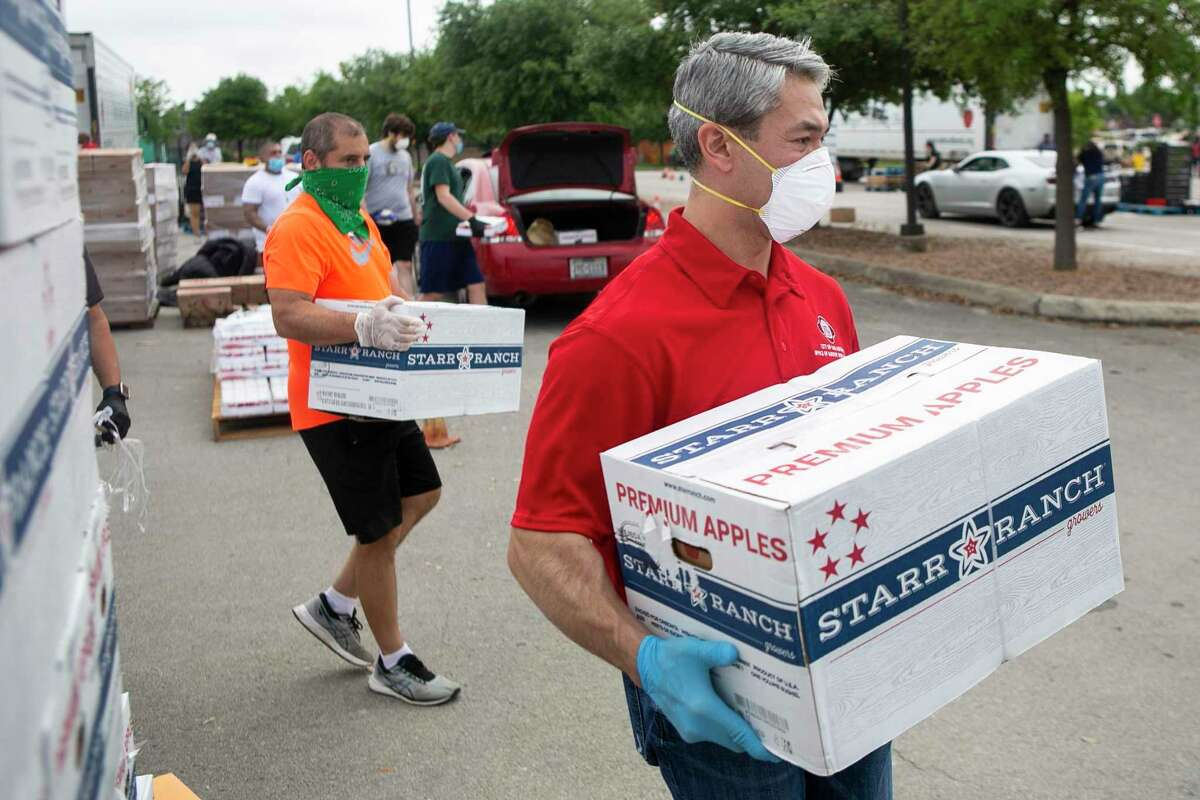 San Antonio Mayor Ron Nirenberg carries a box of apples to a vehicle during the San Antonio Food Bank drive-through food distribution on Tuesday, April 7, 2020, in the Toyota Field parking lot in San Antonio, Texas.