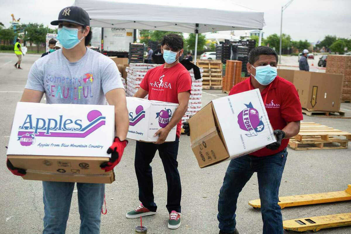 Another San Antonio Food Bank distribution event will be held at Toyota Field on Friday, April 24. Pre-registration is required. At a recent food giveaway, San Antonio Food Bank volunteers wore masks while loading boxes of apples into a waiting vehicle.