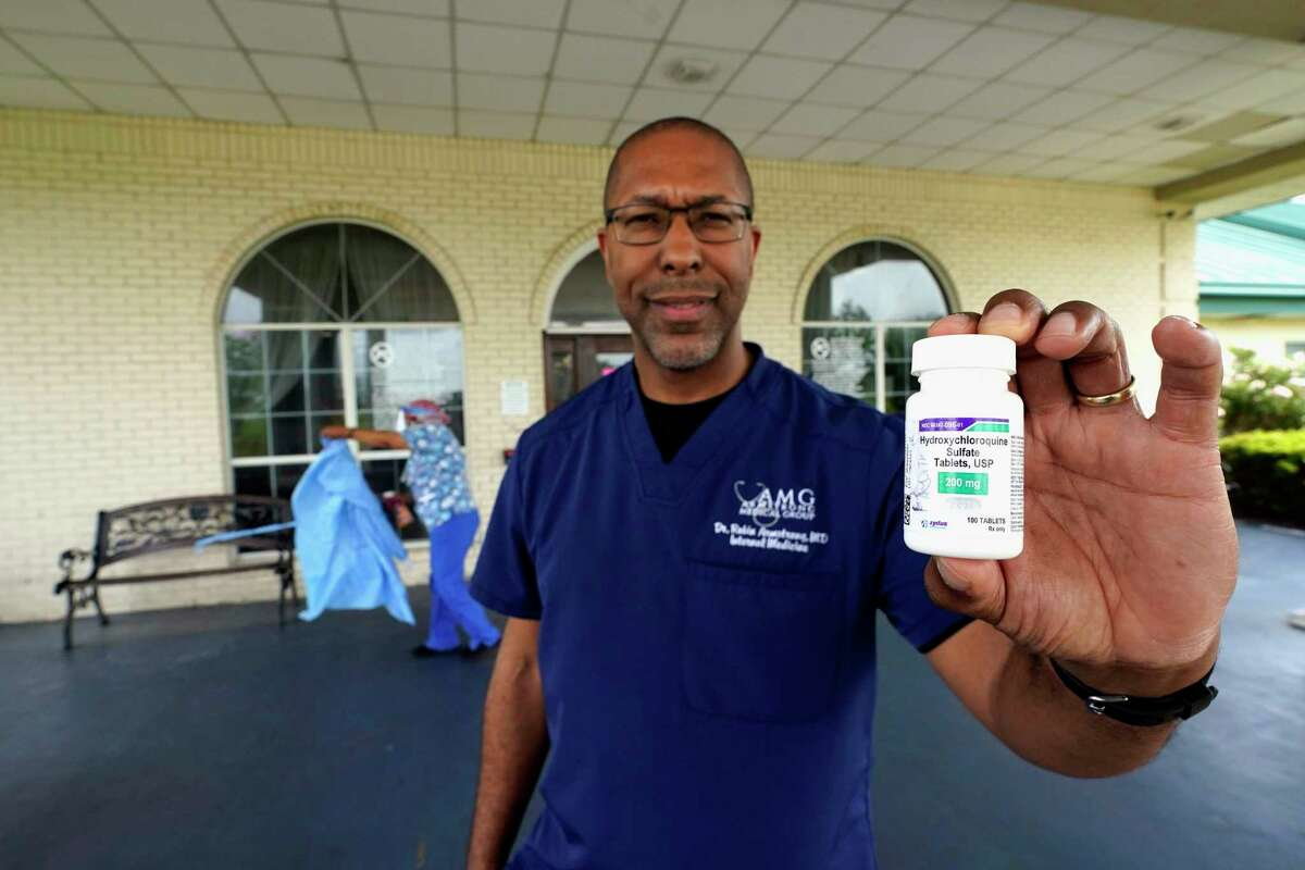Dr. Robin Armstrong holds a bottle of hydroxychloroquine while posing outside The Resort at Texas City nursing home, where he is the medical director, Tuesday, April 7, 2020, in Texas City, Texas.