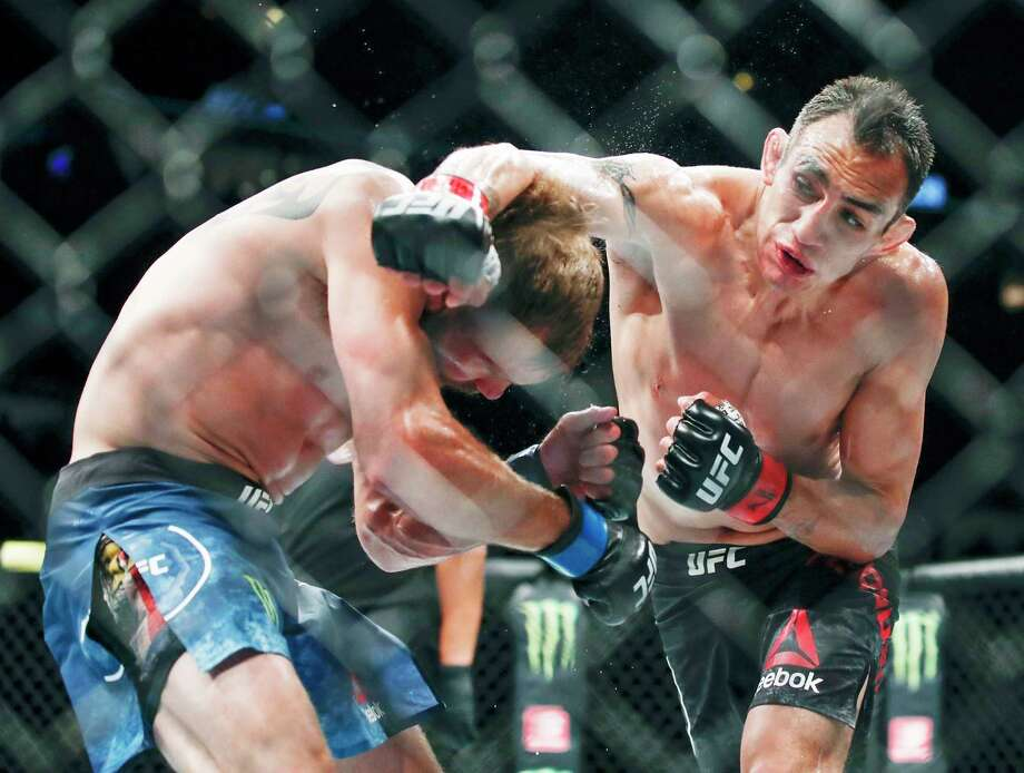 FILE - In this June 8, 2019, file photo, Tony Ferguson, right, punches Donald Cerrone, left, during their lightweight mixed martial arts bout at UFC 238 in Chicago. The UFC says Ferguson will fight Justin Gaethje for the interim lightweight title in the main event of UFC 249 on April 18, 2020. The mixed martial arts promotion announced the matchup Monday, April 6, 2020. Gaethje replaces lightweight champ Khabib Nurmagomedov, who is apparently unable to leave Russia during the coronavirus pandemic. (AP Photo/Kamil Krzaczynski, File) / Copyright 2019 The Associated Press. All rights reserved.