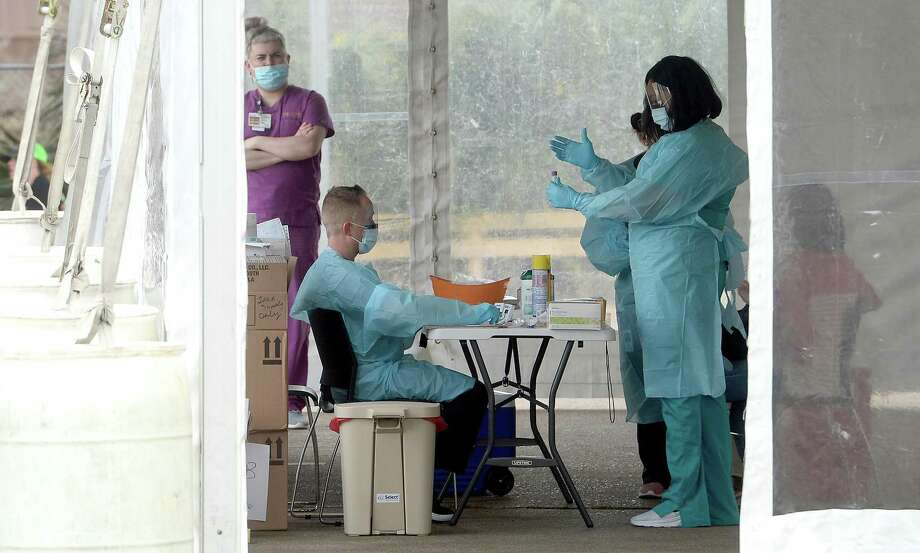 Medical personnel work inside a tent set up in the back lot of Legacy Community Health on N. Eleventh Street in Beaumont offering COVID-19 testing after screening and also doing flu testing. The clinic is the first private screening unit set up in Jefferson County. Photo taken Wednesday, March 18, 2020 Kim Brent/The Enterprise Photo: Kim Brent / The Enterprise / BEN