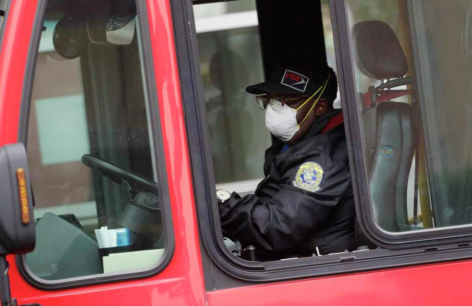 A VIA bus driver wears a protective mask and gloves as he drives through downtown San Antonio last week. Starting Wednesday, VIA will allow no more than 16 passsengers per bus so they can space themselves with empty seats between them. (AP Photo/Eric Gay) Photo: Eric Gay /Associated Press / Copyright 2020 The Associated Press. All rights reserved.