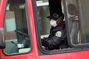 A VIA bus driver wears a protective mask and gloves as he drives through downtown San Antonio last week. Starting Wednesday, VIA will allow no more than 16 passsengers per bus so they can space themselves with empty seats between them. (AP Photo/Eric Gay)