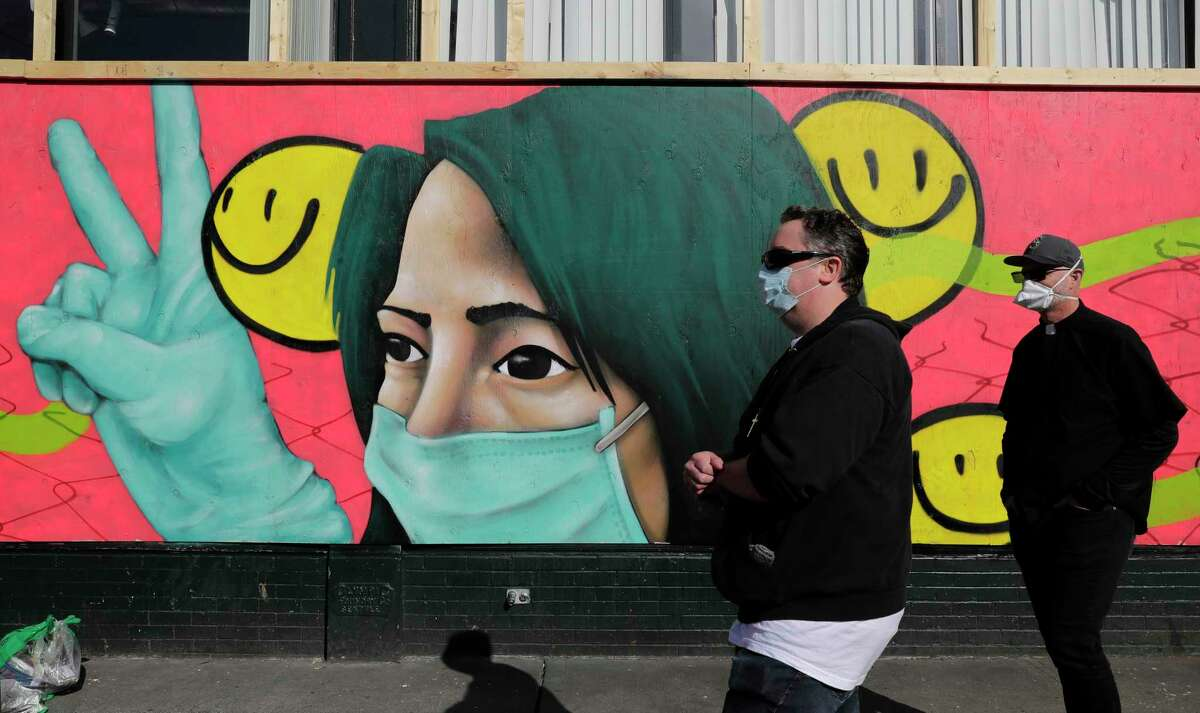 Pedestrians walk past coronavirus-themed artwork of a person wearing a mask and gloves that was painted by street artists @theydrift and @ksra_ksra on a boarded-up business in Seattle's Capitol Hill neighborhood, Tuesday, April 7, 2020. Street art has sprung up on boards covering the windows of many businesses in the area closed temporarily due to the outbreak of the coronavirus.