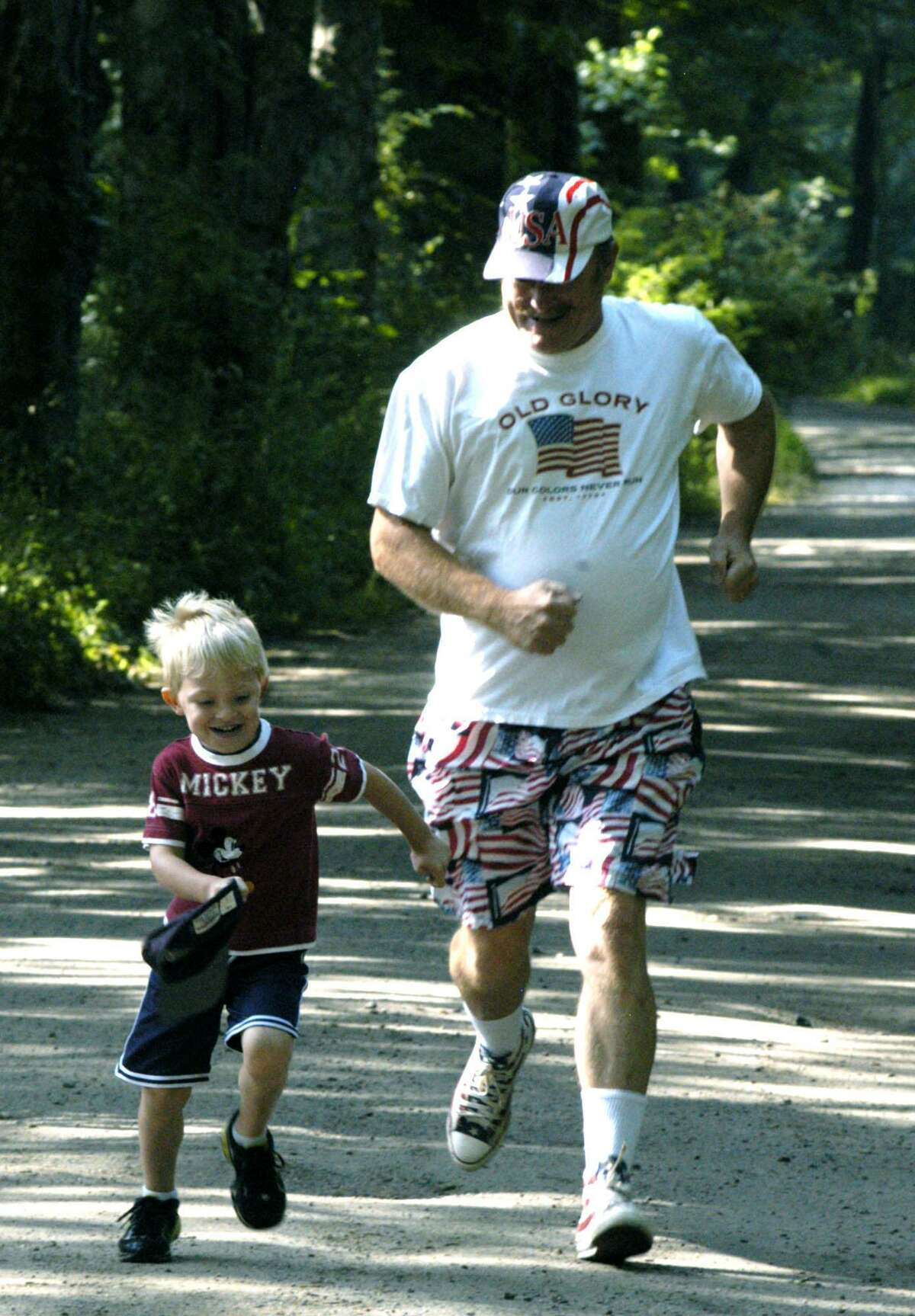 Former First Selectman Mark Lyon is shown in this 2012 photograph doing his best to match strides with his grandson Travis Lipinsky during the 2012 Stephen Reich 5K Freedom Run at Steep Rock Reservation in Washington.