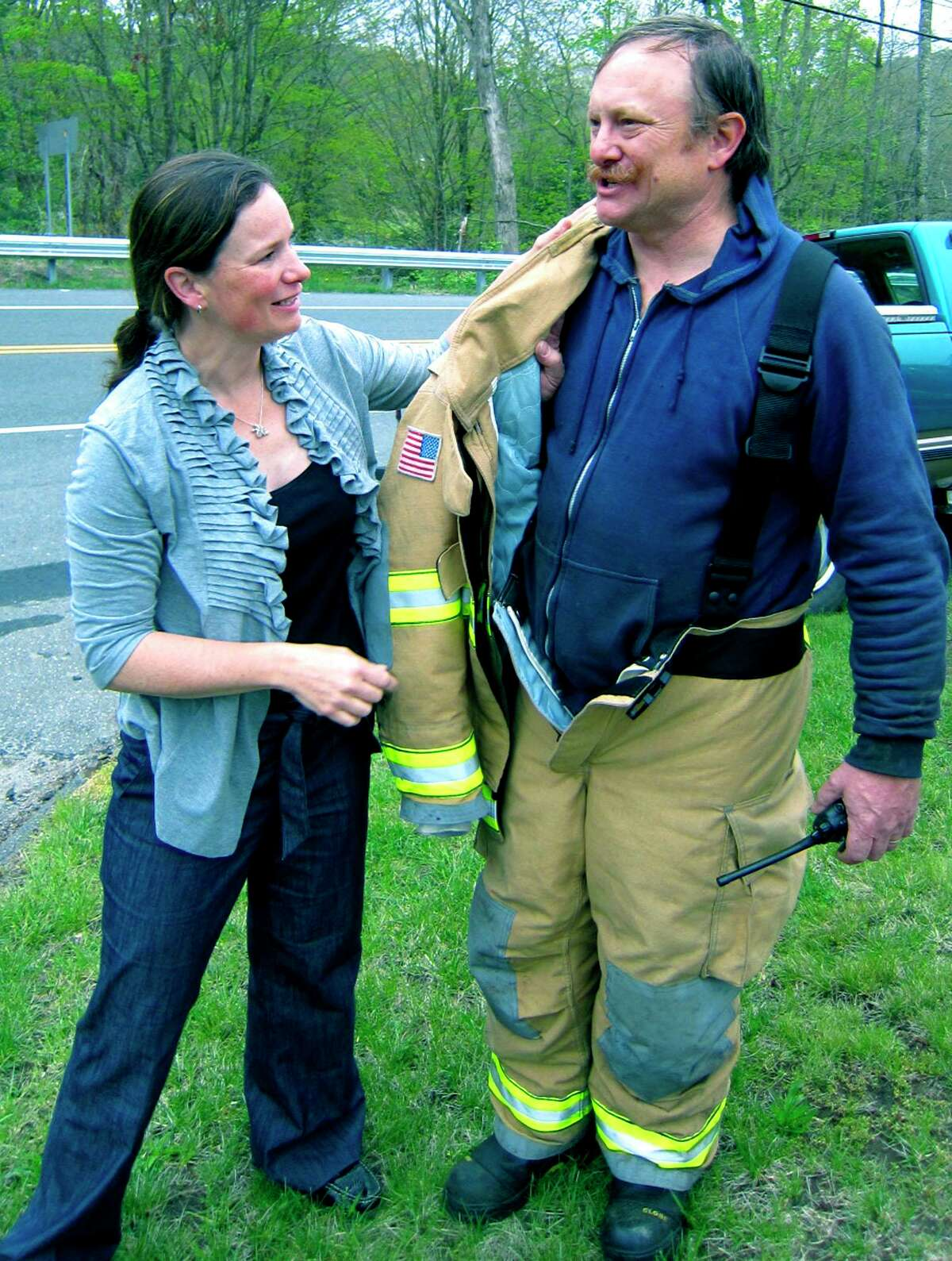 Leah Smith commiserates in May 2012 with then-first selectman and volunteer firefighter Mark Lyon after a fire had ravaged the town's highway garage.