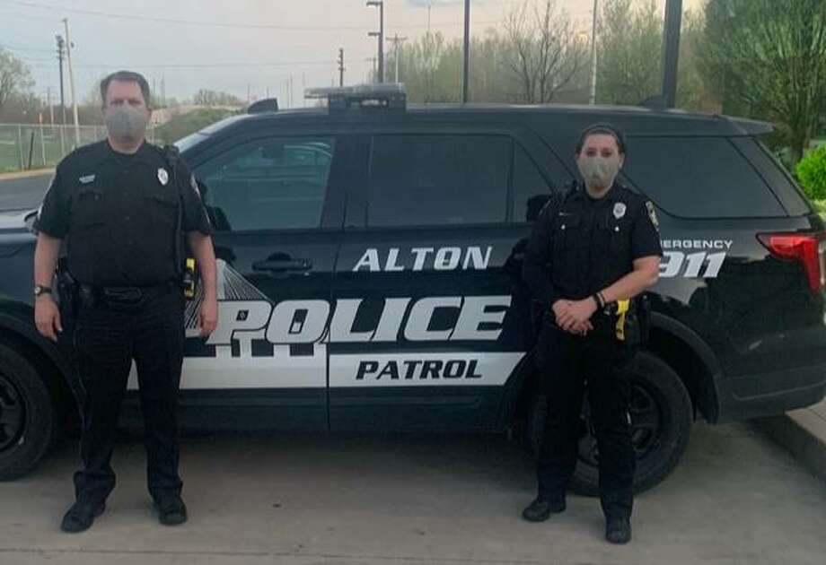 Two Alton Police Department members are pictured near a squad car Tuesday while wearing masks provided by Madison County Masks. Since March 19 the effort has provided more than 500 facial masks for first responders and health care workers. Photo: Contributed|For The Telegraph