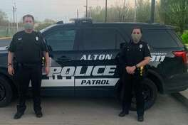 Two Alton Police Department members are pictured near a squad car Tuesday while wearing masks provided by Madison County Masks. Since March 19 the effort has provided more than 500 facial masks for first responders and health care workers.