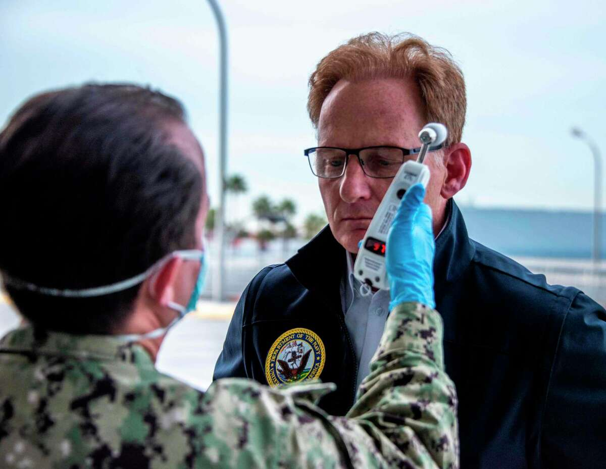 This US Navy handout photo released March 31, 2020 shows Acting Secretary of the Navy Thomas B. Modly having his temperature read as part of a COVID-19 screening prior to a tour of the Military Sealift Command hospital ship USNS Mercy (T-AH 19) and the Los Angeles World Cruise Center, March 31, 2020. - Mercy deployed in support of the nations COVID-19 response efforts, and will serve as a referral hospital for non-COVID-19 patients currently admitted to shore-based hospitals. This allows shore base hospitals to focus their efforts on COVID-19 cases. One of the Department of Defenses missions is Defense Support of Civil Authorities. DOD is supporting the Federal Emergency Management Agency, the lead federal agency, as well as state, local and public health authorities in helping protect the health and safety of the American people. (Photo by 2nd Class Natalie M. Byers / US NAVY / AFP) / RESTRICTED TO EDITORIAL USE - MANDATORY CREDIT