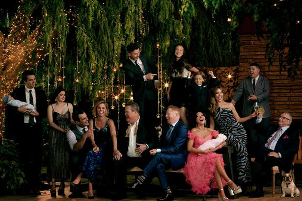 "This image released by ABC shows the cast of the ABC sitcom ""Modern Family,"" from left, Reid Ewing, Ariel Winter, Ty Burrell Julie Bowen, Eric Stonestreet, Nolan Gould, standing left center, Jesse Tyler Ferguson, Aubrey Anderson-Emmons, standing center right, Jeremy Maguire, Sarah Hyland, seated holding baby, SofA-a Vergara, Rico Rodriguez and Ed O'Neill. The comedy will air its series finale after 11 seasons on April 8, the network announced on Wednesday. (Jill Greenberg/ABC via AP)"