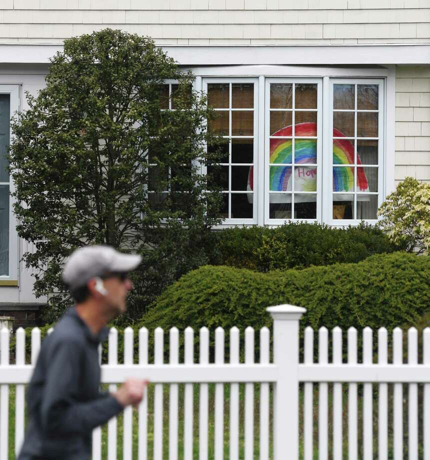 A drawing of a rainbow is displayed in the windows of a home in Old Greenwich, Conn. Sunday, April 5, 2020. Notes of encouragement, drawings, and teddy bears are being displayed in the windows of many homes as a way to bring together community during a time of quarantine and social distancing. Photo: Tyler Sizemore / Hearst Connecticut Media / Greenwich Time