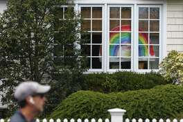 A drawing of a rainbow is displayed in the windows of a home in Old Greenwich, Conn. Sunday, April 5, 2020. Notes of encouragement, drawings, and teddy bears are being displayed in the windows of many homes as a way to bring together community during a time of quarantine and social distancing.