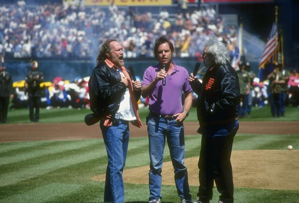 Left to right, Grateful Dead band members Vince Welnick, Bob Weir and Jerry Garcia sing during a game between the Florida Marlins and the San Francisco Giants on April 12, 1993.
