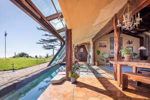 Mid-century and one of a kind, this $4.75M Bolinas home, constructed from wood salvaged from the Gualala River features a 65 foot glass wall opening toward the Pacific Ocean