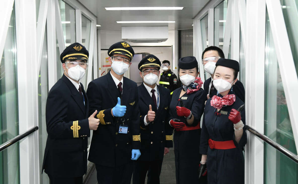 WUHAN, April 8, 2020. Crew members of flight MU2527 of China Eastern airlines pose for photos before takeoff at the Tianhe International Airport in Wuhan, central China's Hubei Province, April 8, 2020. Wuhan on Wednesday lifted outbound travel restrictions, after almost 11 weeks of lockdown to stem the spread of COVID-19. (Photo by Cheng Min/Xinhua via Getty) (Xinhua/Cheng Min via Getty Images)