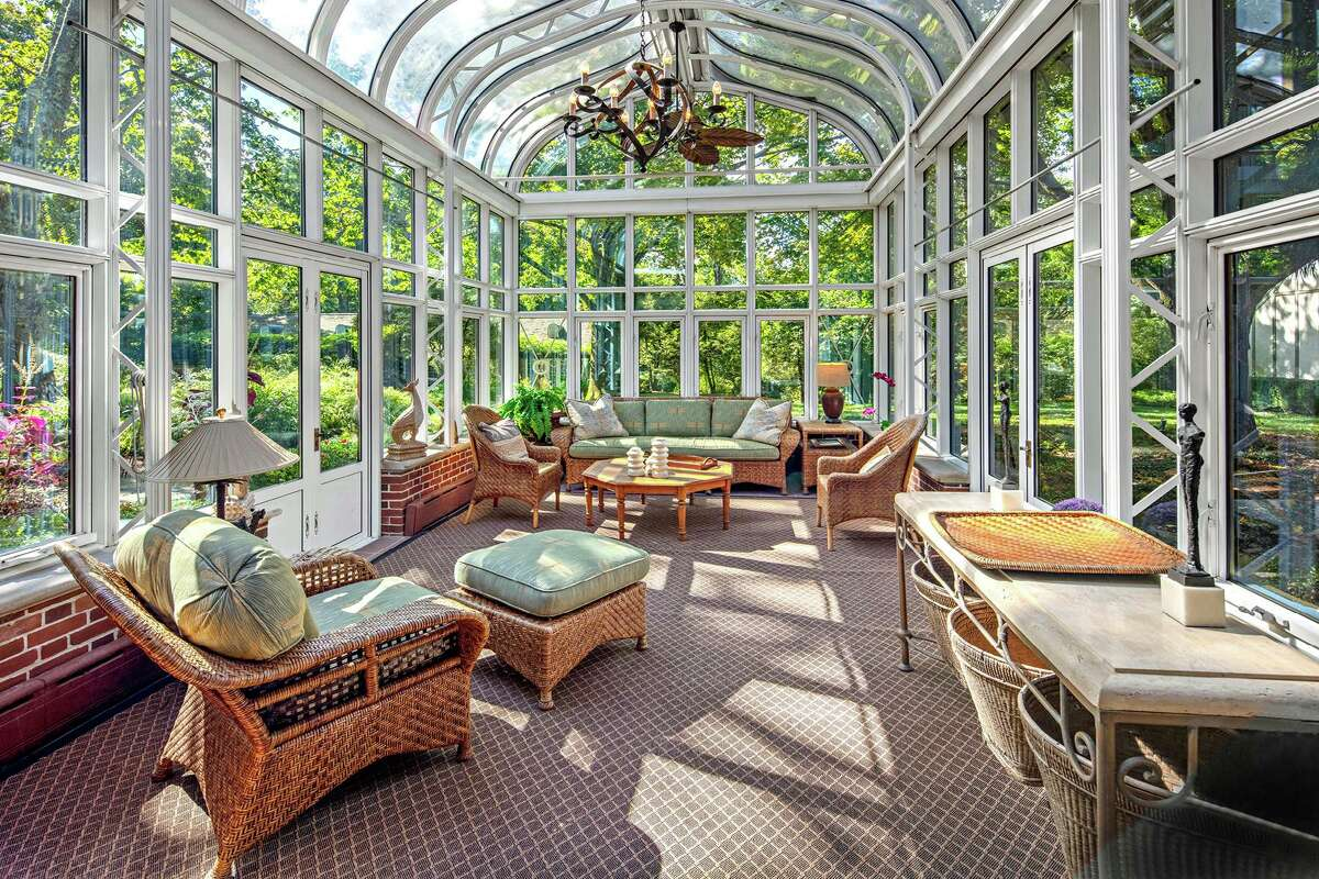 The two-story glass conservatory features a potting table and sink (not pictured), and doors to the attractive grounds.