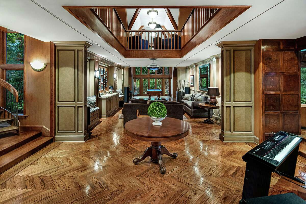 The two-story media wing features a herringbone-patterned hardwood floor and houses a family room with a home movie theater system, home office, and billiard room.