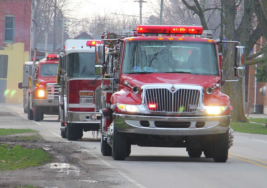 Emergency vehicles from the ACW-Unionville Fire Department drive by the home of Claire Van Tol on Tuesday evening to wish her a happy 14th birthday. The department has been conducting the parades to cheer up homebound kids during a challenging time. Photo: Mark Birdsall/Huron Daily Tribune