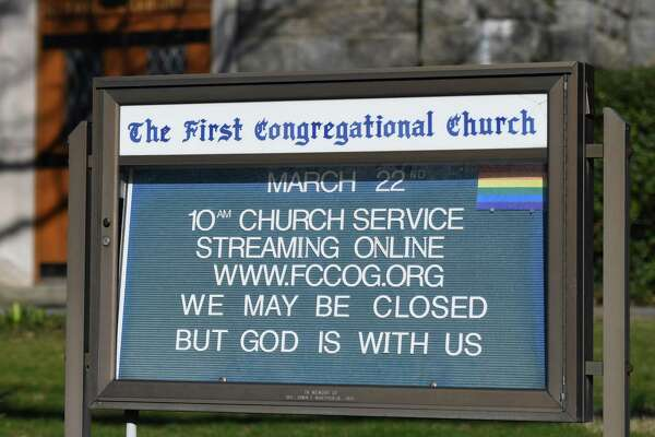 A sign is displayed telling of church services streamed online outside First Congregational Church of Greenwich in Old Greenwich.