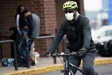 A man wearing a mask to try and prevent the spread of COVID-19, known as coronavirus, arrives on a bicycle at a supermarket in Washington, D.C.