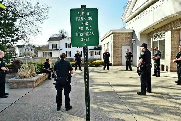 Branford police officers practice social distancing outside police headquarters and in front of their sergeant during roll call Monday before going on patrol during the second shift.