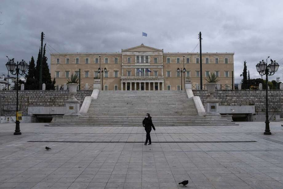 A woman wearing a protective face mask walks at deserted Syntagma square in Athens on April 7, 2020. Photo: Bloomberg Photo By Yorgos Karahalis / © 2020 Bloomberg Finance LP