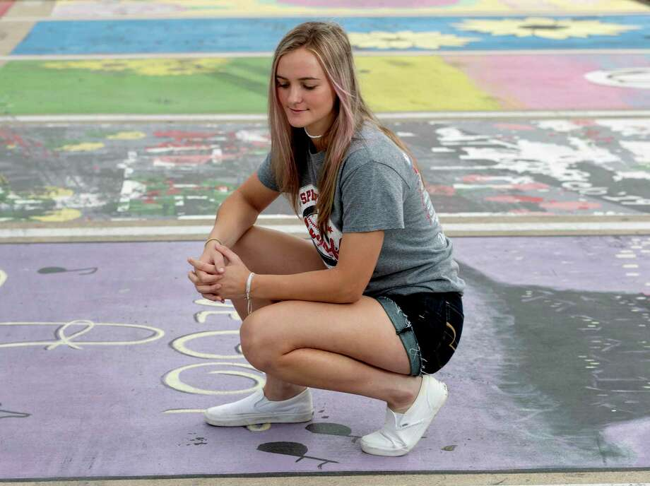 "Shaelyn Sanders poses for a portrait at her painted parking spot at Splendora High School, Thursday, March 26, 2020, in Splendora. ""The COVID-19 pandemic has definitely turned my senior year around, I went from counting down the days till graduation to hoping I would even get one. It has all happened so fast; this virus may be taking away a few of the memories I've been looking forward to since I was a little girl. I may not get my last year of high school softball, prom, or a graduation. I wish this would have never happened, but I am trying to be positive and make the best out of the time off."" Photo: Jason Fochtman, Houston Chronicle / Staff Photographer / 2020 © Houston Chronicle"