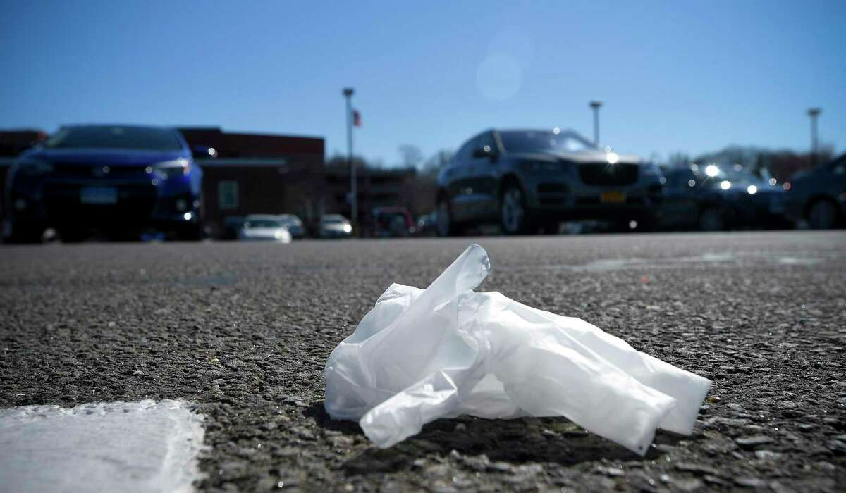 Discarded plastic rubber gloves are photographed on March 27, 2020 in a parking lot of a local shopping market in Stamford.