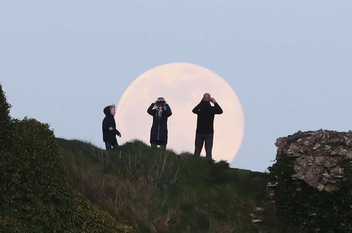 A pink supermoon rises over the Rock of Dunamase in County Laois in the Republic of Ireland. Despite its name, there is no actual colour change to the appearance of the lunar surface - it is a Northern Native American reference to an early-blooming wildflower, which starts to pop up in the US and Canada at the beginning of spring. (Photo by Niall Carson/PA Images via Getty Images)