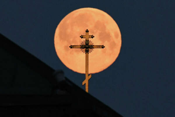 This picture taken early on April 8, 2020 shows the closest supermoon to the Earth, also known as a pink moon, behind the cross on a church in downtown Moscow. (Photo by Kirill KUDRYAVTSEV / AFP) (Photo by KIRILL KUDRYAVTSEV/AFP via Getty Images)