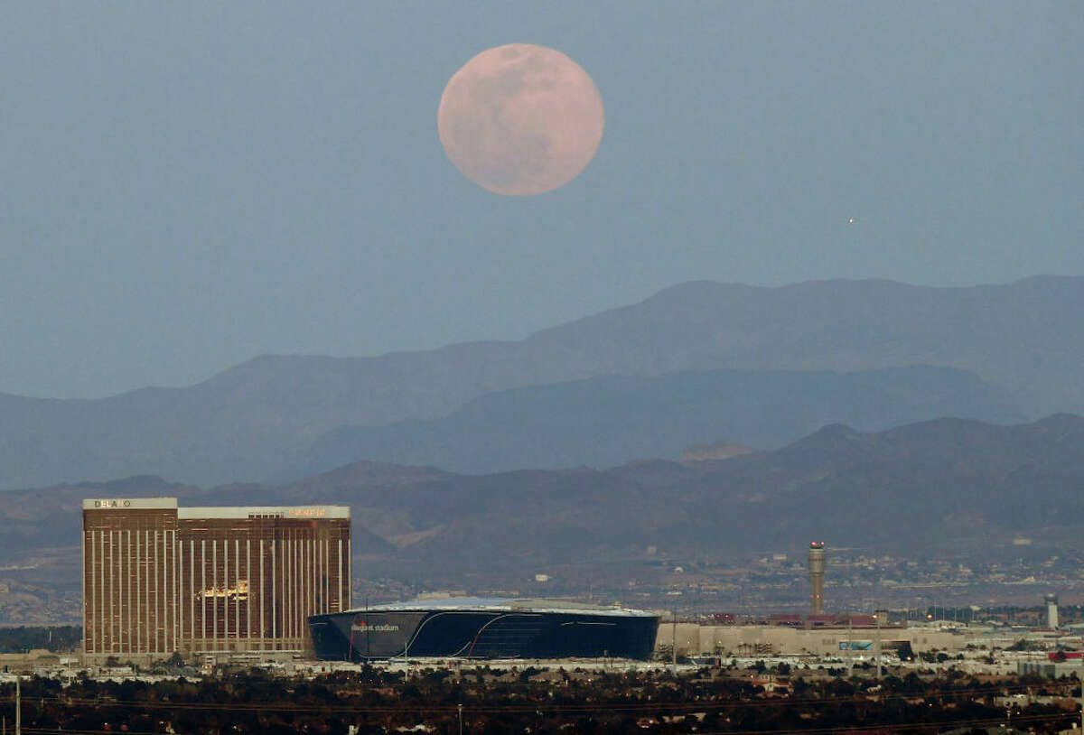 LAS VEGAS, NEVADA - APRIL 07: The super pink moon, the biggest supermoon of the year, rises over (L-R) Delano Las Vegas at Mandalay Bay Resort and Casino, Mandalay Bay Resort and Casino, the under construction Allegiant Stadium and McCarran International Airport on April 7, 2020 in Las Vegas, Nevada. The pink moon got its name because the April full moon occurs at the same time as the pink wildflower Phlox subulata blooms in North America. A supermoon occurs when a full moon coincides with its perigee, which is its closest approach to the Earth. (Photo by Ethan Miller/Getty Images)