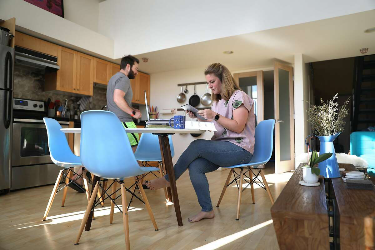 Emily Storms gets ready to teach her fifth grade math class on her kitchen table at home via Zoom as her boyfriend Sean Moore passes by in the background this morning on Tuesday, April 7, 2020, in San Francisco, Calif.