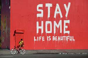 "A man rides his bicycle past a mural reading ""Stay Home / Life Is Beautiful"" during the coronavirus (Covid-19) pandemic on April 3, 2020 in Los Angeles, California. (Photo by Robyn Beck / AFP) (Photo by ROBYN BECK/AFP via Getty Images)"
