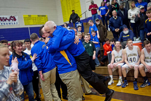 Midland High coach Eric Krause is lifted off the ground by assistant coach Scott Robertson following the Chemics' win over Saginaw High in a March 16, 2016 Class A regional final at Bay City Central.