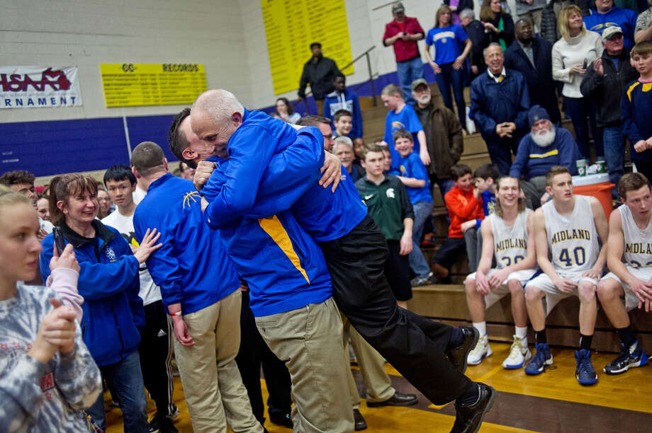 Midland High coach Eric Krause is lifted off the ground by assistant coach Scott Robertson following the Chemics' win over Saginaw High in a March 16, 2016 Class A regional final at Bay City Central. Photo: Daily News File Photo