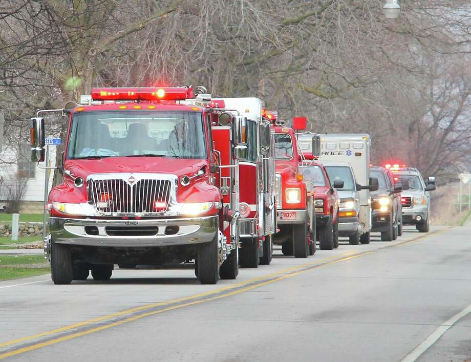 Emergency vehicles from the ACW-Unionville Fire Department drive by the home of Claire Van Tol on Tuesday evening to wish her a happy 14th birthday. The department has been conducting the parades to cheer up homebound kids during a challenging time. For more photos, go to www.michigansthumb.com. (Mark Birdsall/Huron Daily Tribune)
